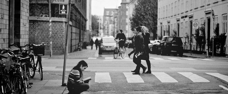Una mujer escribe sola en el bordillo de la calle