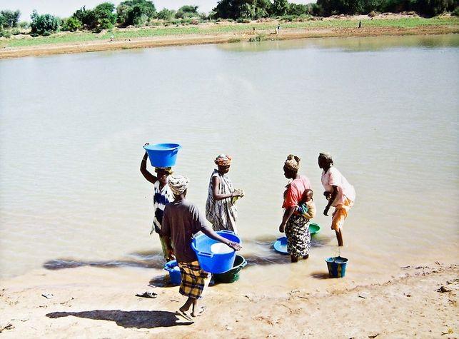 Cinco mujeres africanas cargan con bidones de agua cerca del río