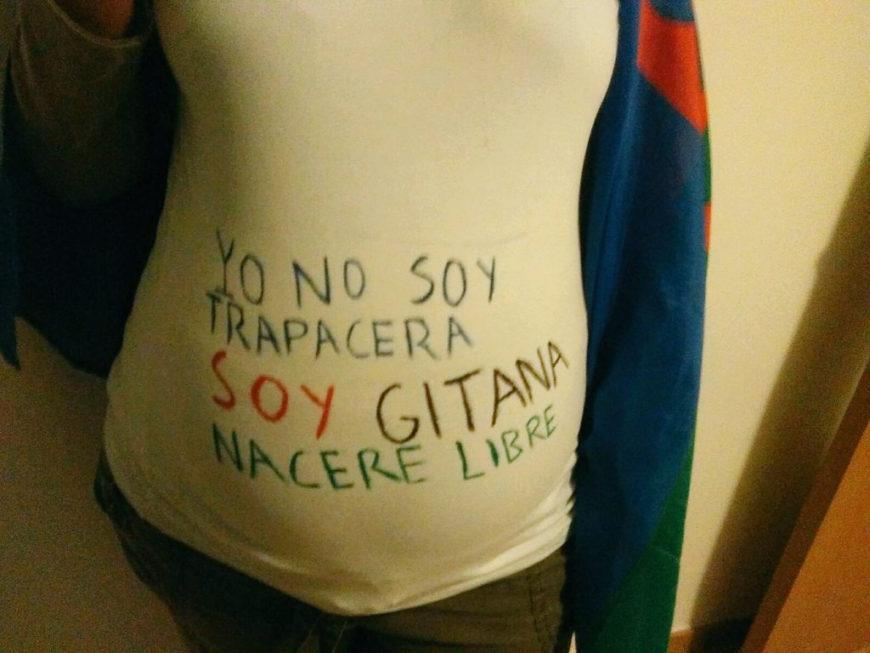 Barriga de una embarazada sobre la cual hay escrito: Yo no soy trapacera, soy gitana, naceré libre