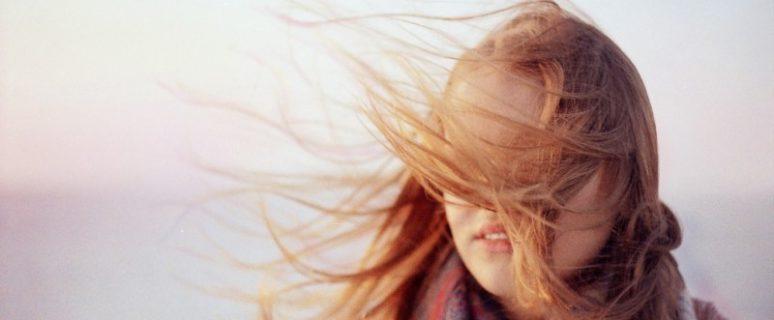 El cabello flota en el viento y cubre los ojos de una mujer con el pelo castaño