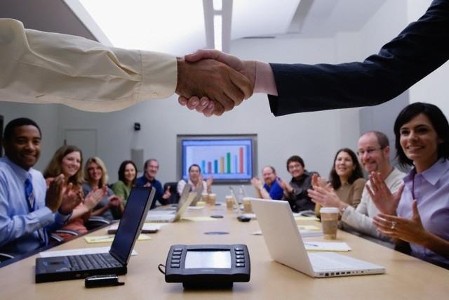 Reunión empresarial alrededor de una mesa en la que participan hombres y mujeres en igual cantidad