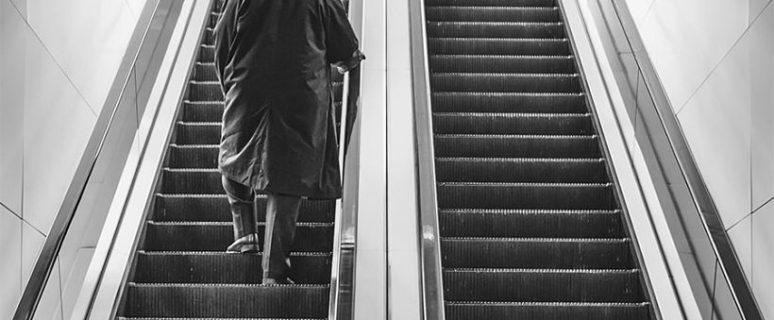 Un hombre aparece de espaldas subiendo unos escalones en una foto en blanco y negro