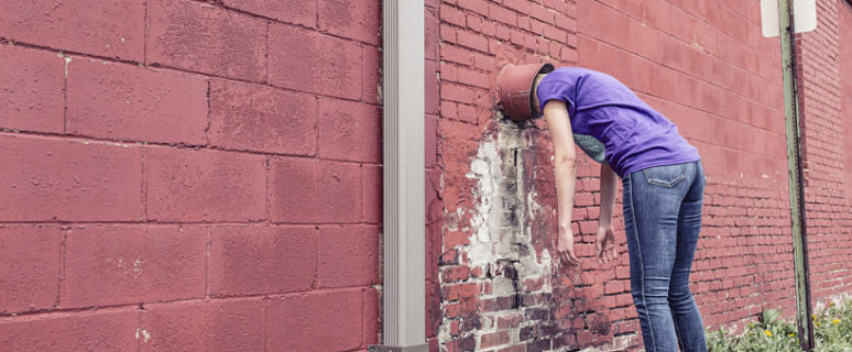 Una mujer con un cubo en la cabeza se da contra un muro