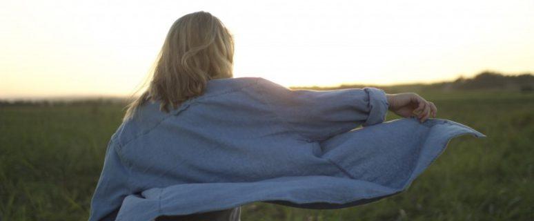 Una mujer camina en un terreno de hierba y el viento hace volar su chaqueta