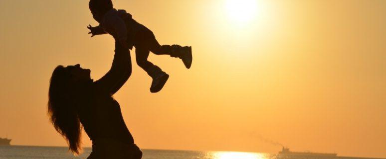 Foto a contraluz de una madre alzando a su bebé en el aire