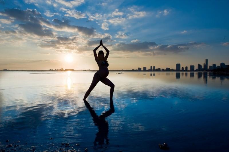 Silueta de una mujer embarazada practicando yoga en un paisaje natural de playa