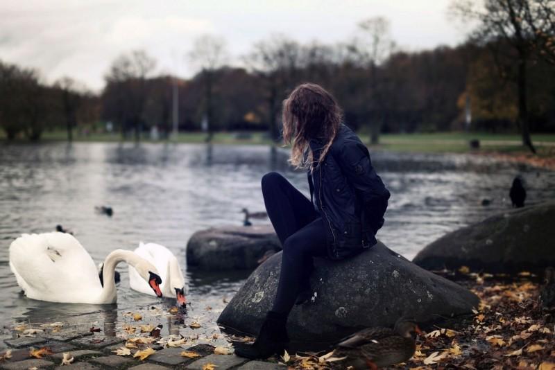 Una mujer con un posado triste permanece sentada sobre una roca en un lago con cisnes al lado