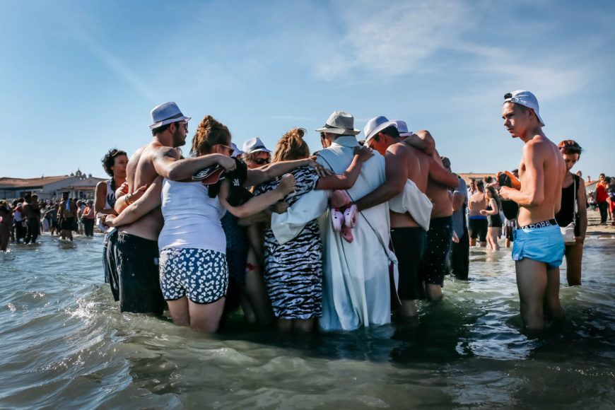 Tras caminar hasta el mar para sumergir la imagen de Sara, muchas familias aprovechan para bautizar a sus niñas y niños. /Foto: Andrea Mantovani