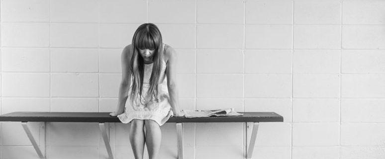 Una mujer aparece sentada en un banco con posado triste y mirando hacia el suelo