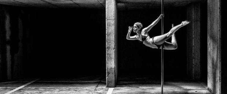 Mujer con figura atlética bailando en la barra de pole dance