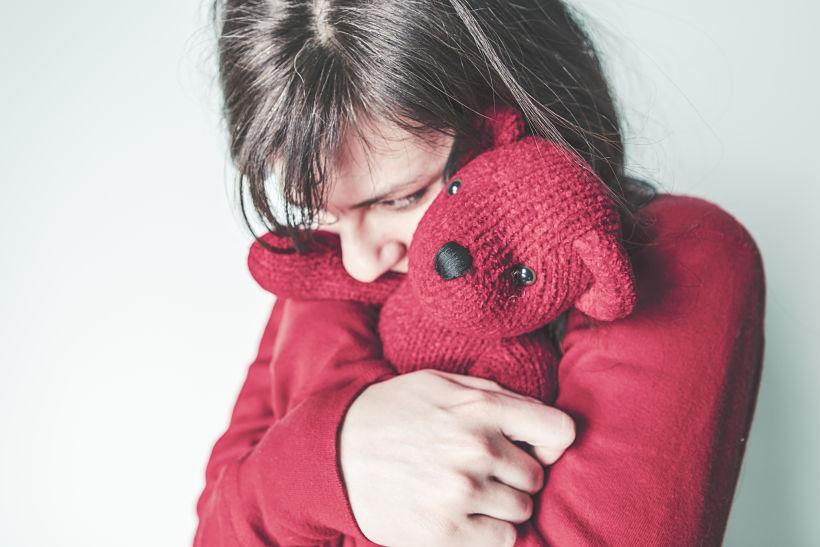Una mujer vestida de rojo abraza con fuerza un osito de lana de color rojo