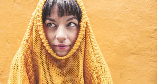 Una mujer se esconde metida en su jersey amarillo que solo deja ver su rostro