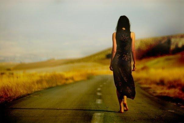 Una mujer camina sola y descalza por una carretera desierta