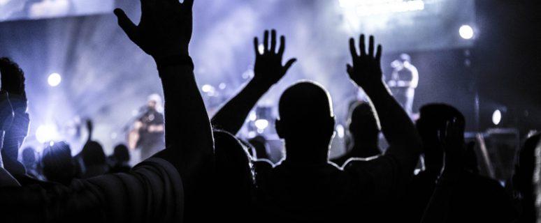 Gente con los brazos alzados en un concierto