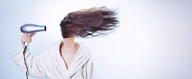 Mujer secandose el pelo con secador de manera brusca ya que el pelo le cubre toda la cara