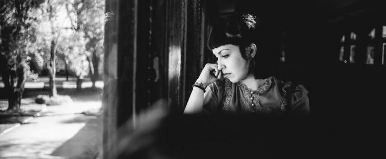 Una mujer mira a través de la ventana de un tren con expresión melancólica