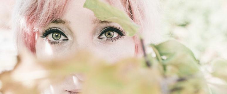 Mirada de una mujer con los ojos verdes y el pelo rosa, escondida detrás de un arbusto