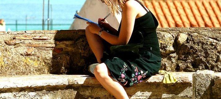 Una mujer escribe en un cuaderno sentada sobre una muralla