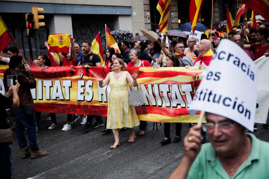 """30 de septiembre. Manifestantes en contra del referéndum avanzan por vía Laietana, felicitando a la Policía Naciona en su paso por la Jefatura Superior de Policía. En Plaza San Jaume se escuchan las consignas de """"Puigdemont a prisión"""" y """"no se votará""""."""