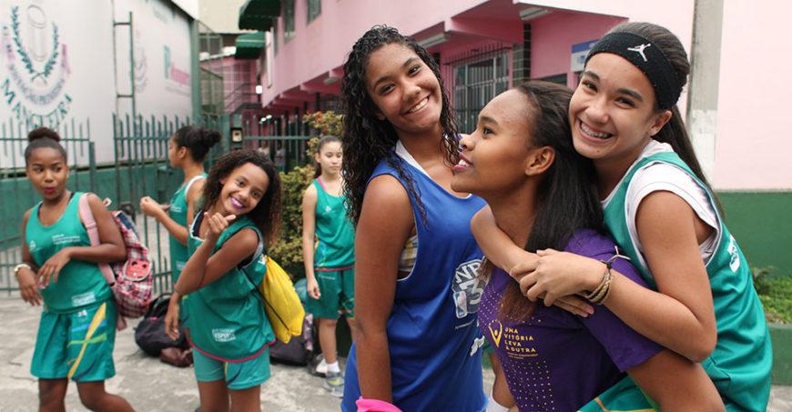 "Tres niñas participantes en ""One Win Leads to Another"" en Brasil celebran durante un partido de baloncesto. Foto: ONU Mujeres/Gustavo Stephan."