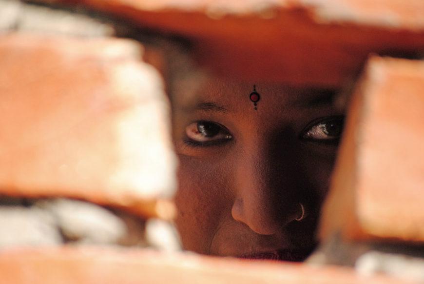 Una mujer mira a través del muro. / Foto: Zeneida Bernabé