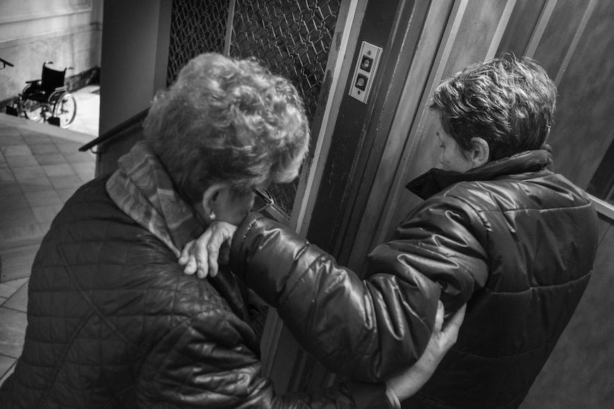 Al salir del ascensor Maribel sujeta a Isabel para que ésta, agarrándose a las viejas rejas del hueco del ascensor, acceda a una barra y, a partir de ahí, pueda empezar a bajar los nueve escalones que la separan de la calle. Nueve escalones que la agotan física y mentalmente, ya que teme caerse algún día. Además, la necesidad de una persona que la sujete, la hace totalmente dependiente para salir a la calle. Isabel sueña con una sencilla rampa/. (c) Patricia Bobillo Rodríguez