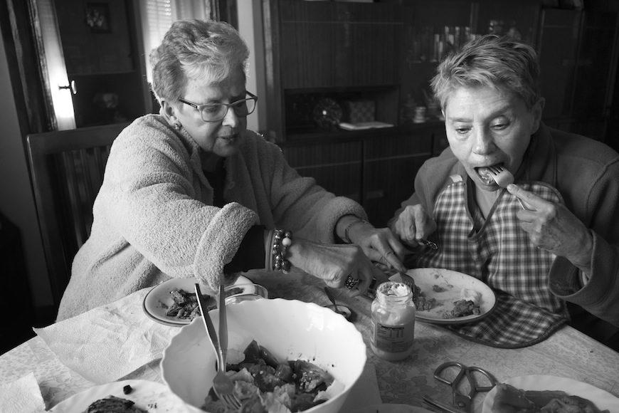 """""""La convivencia es amor"""" dice con voz amable Isabel, que ha tenido que aprender a hablar, a mantener el equilibrio, a controlar los temblores, a peinarse, a comer sola.... Maribel, de 72 años, atiende las necesidades básicas de la vida diaria de Isabel, que intenta, no sin esfuerzo, ser lo más autónoma posible./ (c) Patricia Bobillo Rodríguez"""