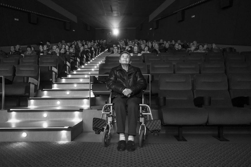 """Isabel mira la película 'La la Land, la ciudad de las estrellas"""" en el cine del centro comercial Las Arenas (Barcelona), donde las personas que van en sillas de ruedas, sólo pueden ubicarse en primera fila, a pocos metros de la pantalla. /.(c) Patricia Bobillo Rodríguez"""