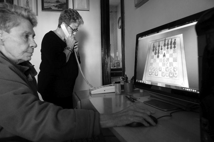 Mientras Isabel juega al ajedrez, Maribel consulta por teléfono el procedimiento para solicitar una silla de ruedas eléctrica. Finalmente la solicitud fue denegada, pero han recurrido./ (c) Patricia Bobillo Rodríguez