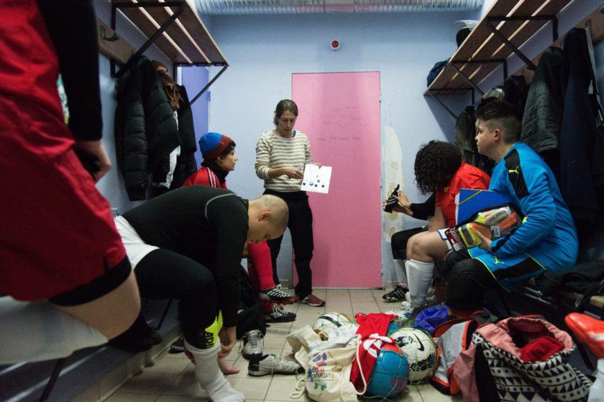 Antes de un partido, las jugadoras se congregan en los vestuarios. Karine, entrenadora suplente, da las últimas instrucciones antes de salir al terreno de juego.