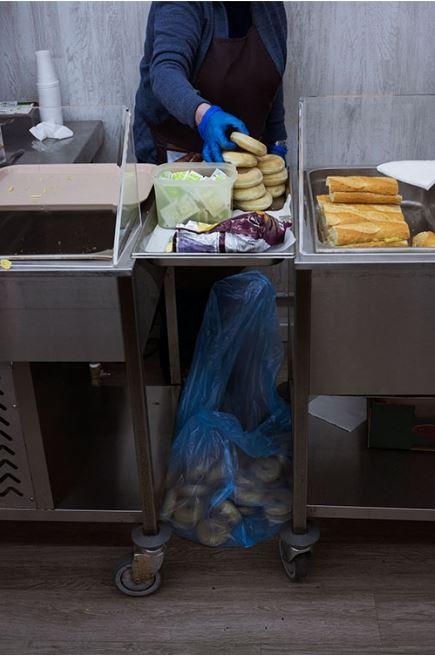 Personal del centro ASSÍS Centro de Acogida sirven el desayuno a las personas que acuden al centro.
