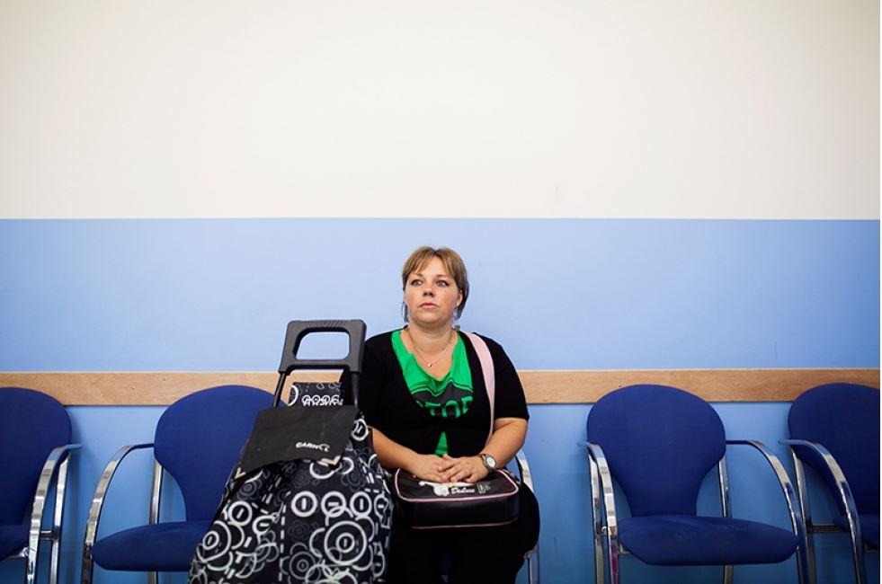 Miriam Coronas espera su paquete de comida en el Punt d'Aliments de la localidad de El Prat (Barcelona). Miriam ya no es usuaria del centro, dice que se olvidó ir un día y le retiraron la ayuda.