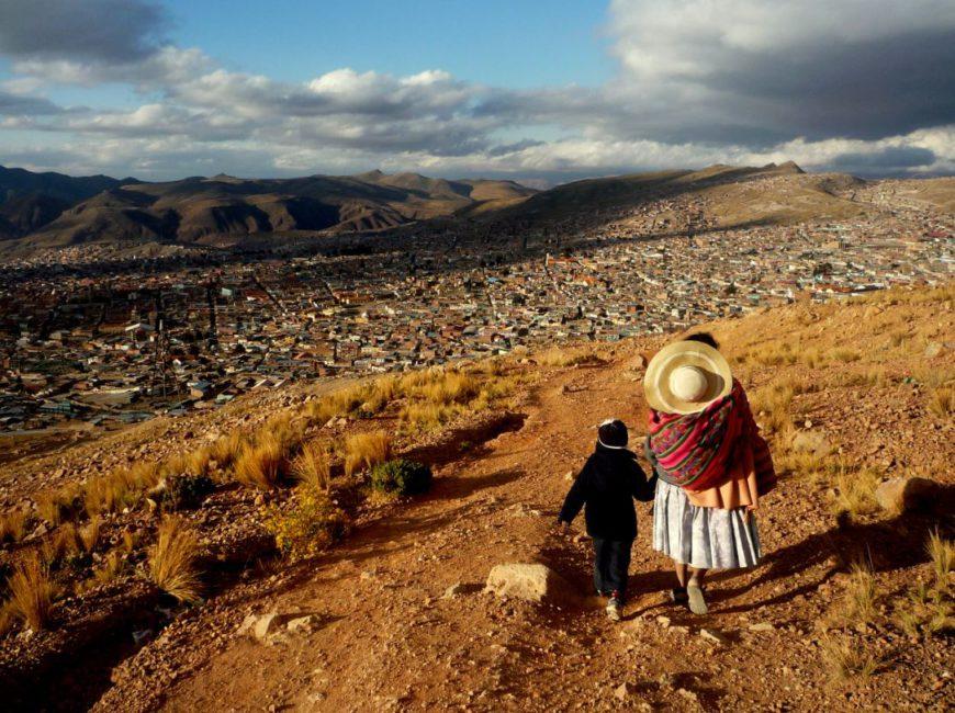Una mujer camina con una criatura con la ciudad de Potosí al fondo. / Foto: Ander Izagirre.