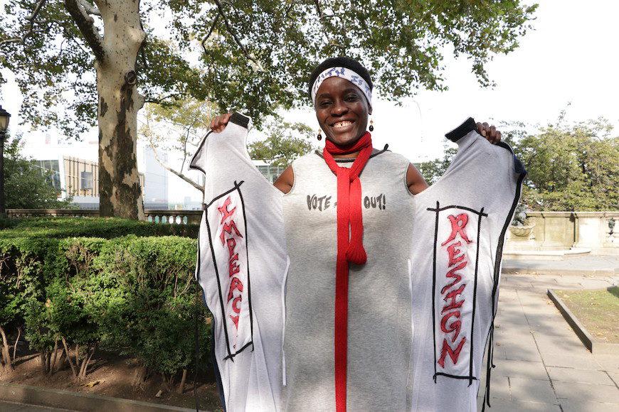 La activista muestra en el interior de su abrigo mensajes como 'Impeach' (Impugna) y 'Resign' (Dimite)./ C.P.