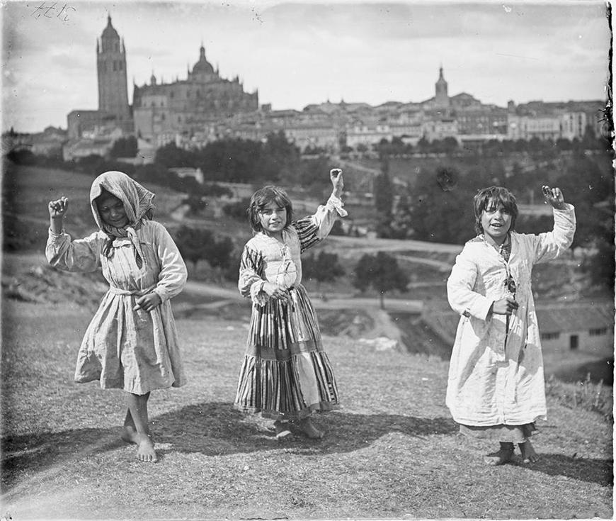 Tres niñas gitanas bailando descalzas con el campo de la ciudad de Segovia tras ellas. Destaca la silueta de la catedral.- Otto Wunderlich