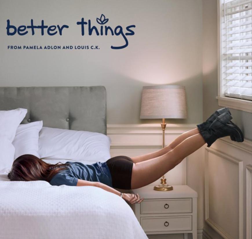 En la imagen se ve a una mujer tumbada boca abajo sobre una cama, con los pies apoyados sobre la ventana que hay al lado.