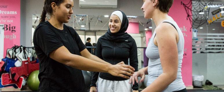 Dos mujeres practican artes marciales bajo la mirada de su entrenadora.