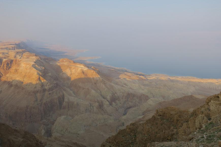 En la imagen se ve el mar desde una montaña rocosa marrón al atardecer.