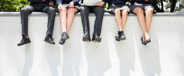 En la imagen se ven cinco adolescentes sentados en lo alto de un muro blanco. Van vestidos con uniforme de colegio azul marino.