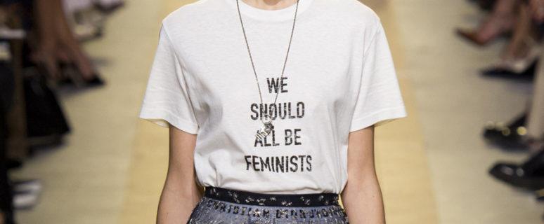 """Foto de una modelo en una pasarela, luciendo una camiseta blanca en la que pone """"Todos deberíamos ser feministas"""" en inglés."""