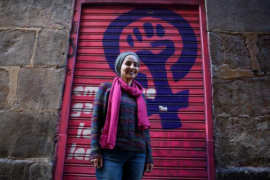 Ahlam Tarayra posa frente a una persiana con un mural feminista, durante su visita a Bilbao./ Aitor Garmedia (Tras los muros)