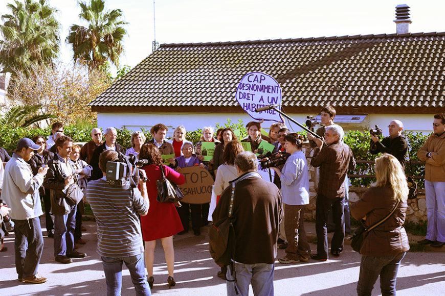 Un montón de gente, con carteles contra los desahucios, se reúnen ante los medios de comunicación. Al fondo se ve a Ada Colau atender a los medios