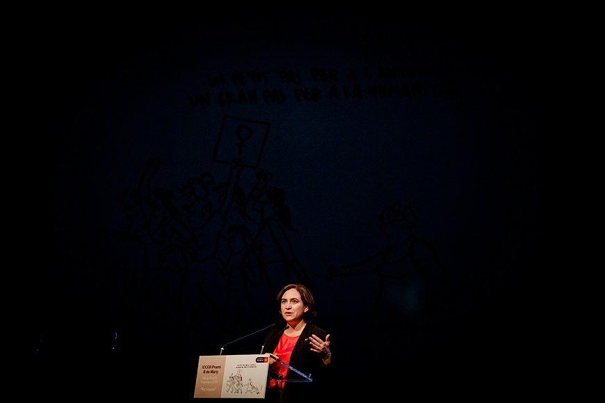 La imagen es completamente negra, excpeto en la parte de abajo y en el centro donde está Ada Colua, vista de lejos, leyendo en un atril.