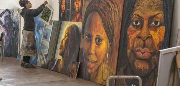 La artista Bianca al fondo colocando un cuadro en una pared llena de grandes de sus obras, pinturas, que reflejan a mujeres negras