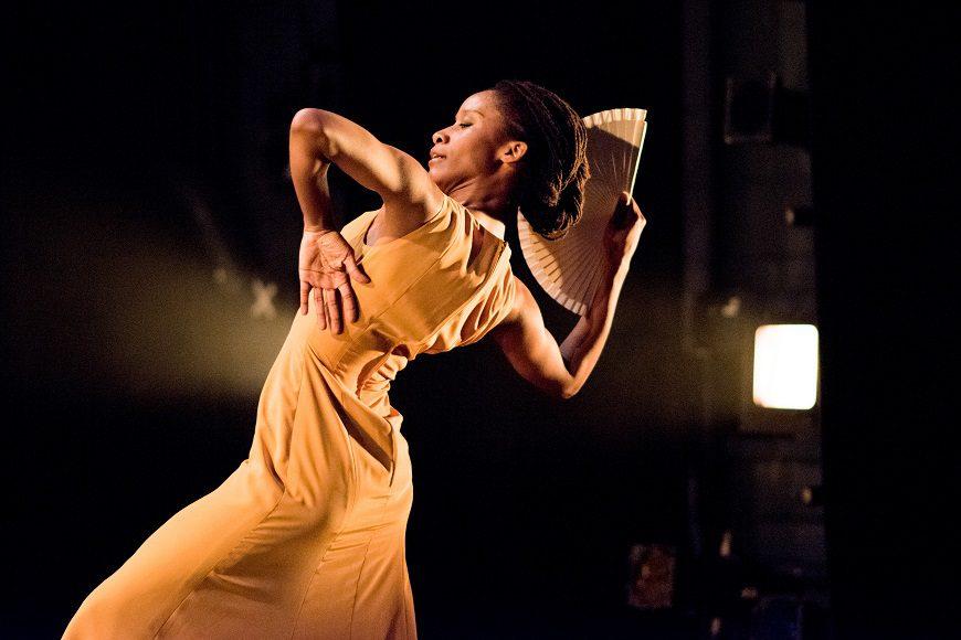 En el centro de la imagen una mujer negra con el pelo recogido, un vestido sin mangas y un abanico en la mano baila flamenco