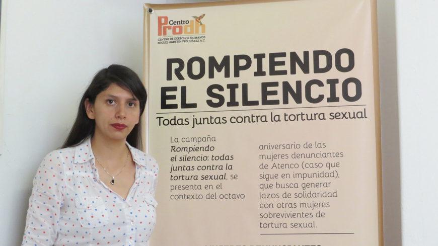 Una mujer posa junto a un cartel que pone 'rompiendo el silencio'