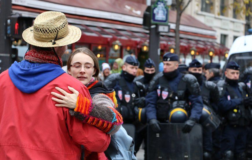 en primer plano una pareja baila agarrada, el hombre de espaldas lleva un sombrero de paja, a la chica, con gafas se la ve la cara. Al fondo, policias antidisturbios
