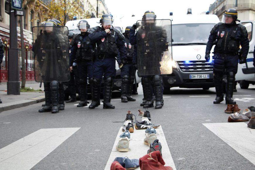en un primer plano se ven zapatos y zapatillas colocados sobre la línea blanca de un paso de cebra, al fondo hay varios policías antidisturbios