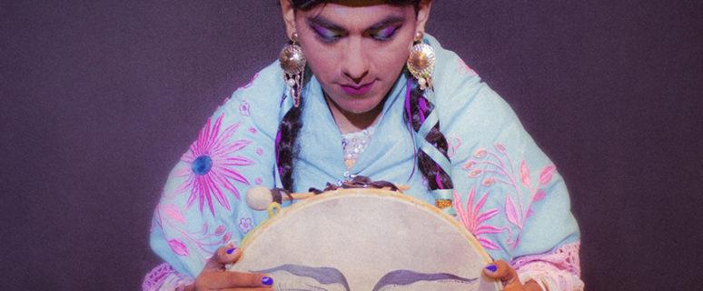 una mujer aymara con el traje típico está sentada en el suelo mirando hacia el suelo y con una pandereta en las manos que tiene pintada una cara