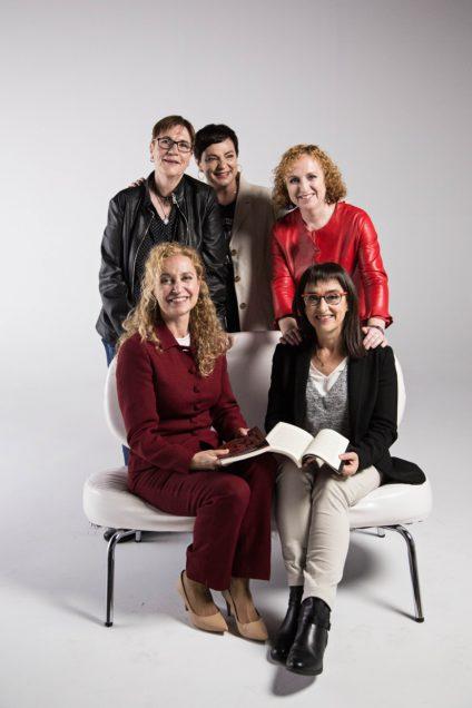 Cinco mujeres en el centro de la imagen posan con un fondo blanco. Dos están sentadas y tres de pie